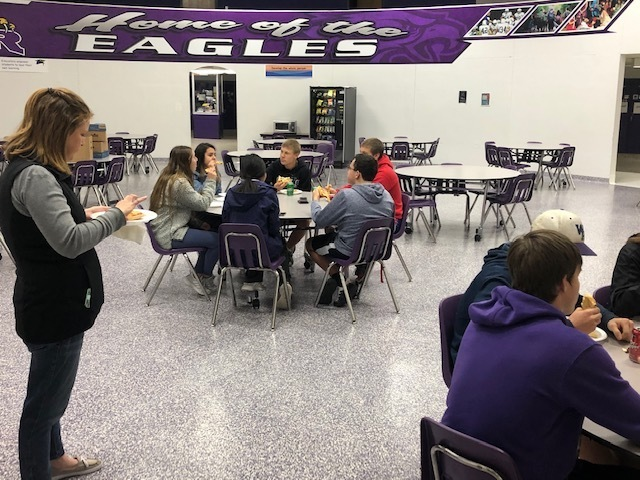 Members enjoying Casey's Pizza after collecting food items.